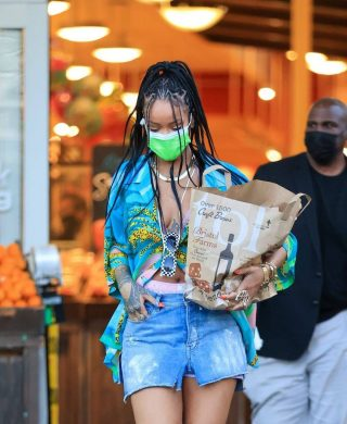 "Rihanna @badgalriri did some shopping in a delightfully summery ensemble, pairing a printed camp collar shirt from Celine Homme's collaboration with artist Tyson Reeder with a distressed denim mini skirt and ankle chain heels by Amina Muaddi. She wore a pink bralet under her loosely buttoned shirt, with pink boxer shorts visible under her skirt. And her accessories were just as excellent: She wore a flat gold chain necklace, a gold watch with several gold bracelets, black and white checkerboard sunglasses (tucked into her shirt), an assortment of statement rings, and a neon green face mask. In very good news, Rihanna's exact shirt is still in stock, retailing at $790 from Mr Porter (the shirt replicates Tyson Reeder's artwork 'Autobahn,' as part of Celine Homme's Spring/Summer 2021 collection ""The Dancing Kid."") In less good news, her shoes—the Henson style by Amina Muaddi in white, as identified by Who What Wear are out of stock pretty much everywhere. And in exceptional news, Rihanna recently hinted that she's releasing a new single. So many emotions in one paragraph!"